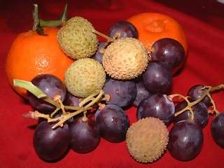 Food Photographs - Picture of Fruit basket of lychees tangerines and black grapes on a bright red cloth