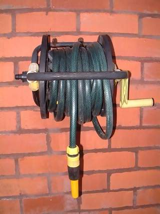Miscellaneous Photographs - Picture of Green host reel with yellow spout and winding handle attached to brick wall