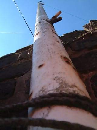 Structures Photographs - Picture of Steel pole against brick wall looking at sky
